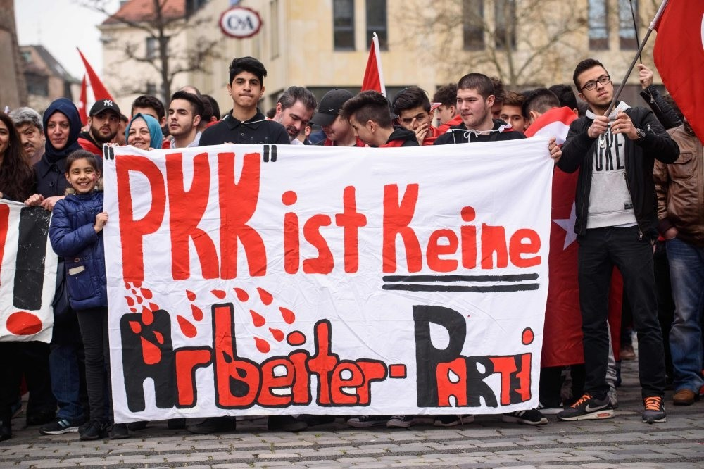 People hold a banner reading ,the PKK is not a worker's party, during the ,Peace March for Turkey,, organized by the new German Turkish Committee on April 10, 2016, in Nuremberg.