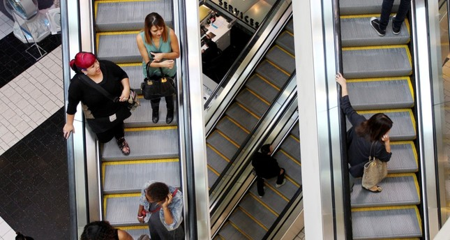 Shoppers ride escalators at the Beverly Center mall in Los Angeles, California, U.S., Nov. 8, 2013.