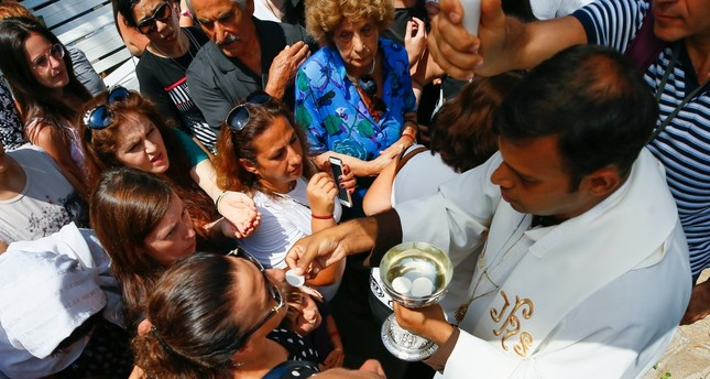 A priest delivering wafers to the faithful at the religious service outside the House of Virgin Mary in İzmir, Aug. 15, 2019.