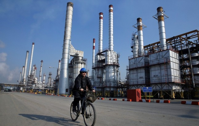 In this Dec. 22, 2014 file photo, an Iranian oil worker rides his bicycle at the Tehran oil refinery, south of the capital Tehran, Iran. AP Photo