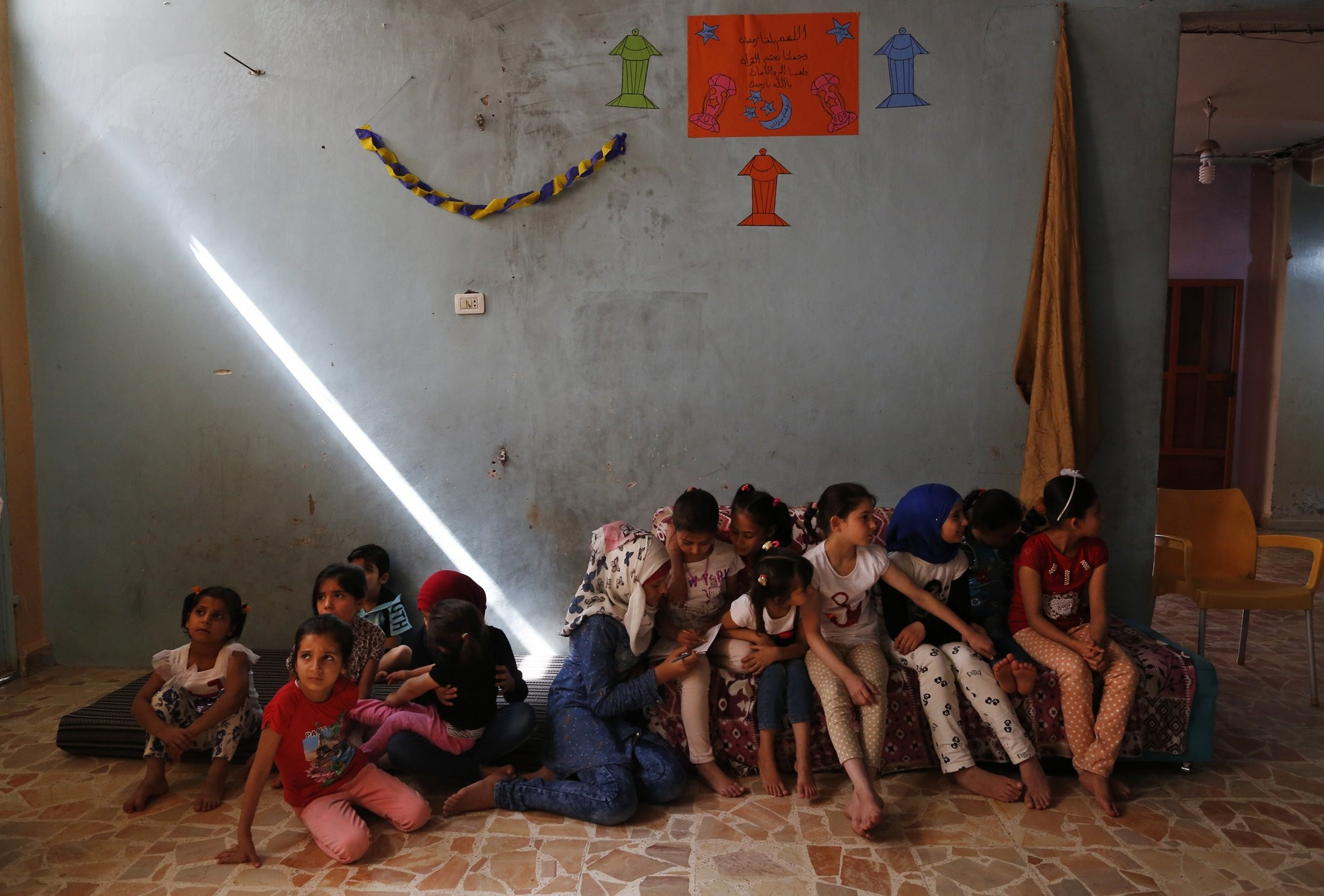 Syrian orphans from Aleppo sit as they pass time in an orphanage in Jarablus.