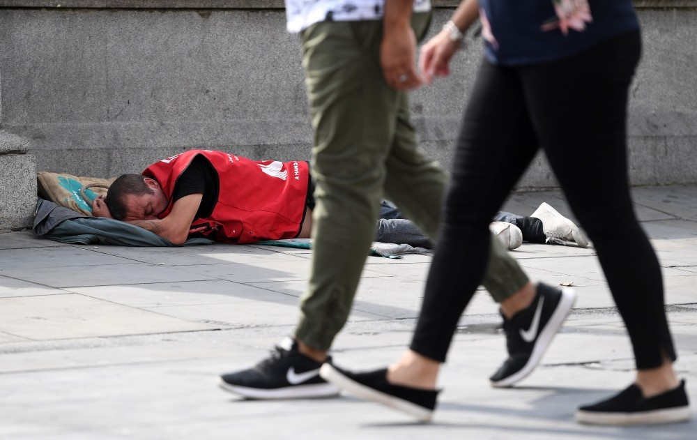 A homeless man sleeps on the pavement in central London, U.K.