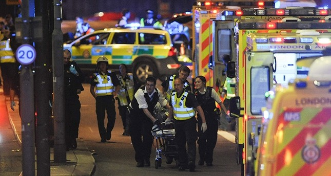 Police officers and members of the emergency services attend to a person injured in an apparent terror attack on London Bridge in central London on June 3, 2017. AFP Photo