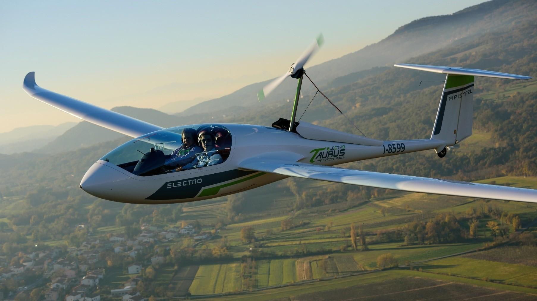 A Pipistrel Taurus Electro electric two-seat airplane flies above Ajdovscina.