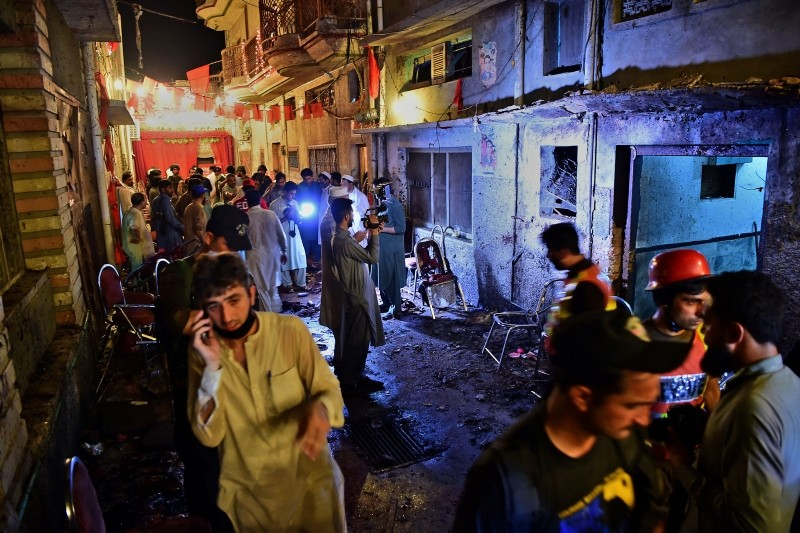 Pakistani security officials and volunteers search the site after a suicide bombing at an election rally in Peshawar on July 10, 2018. (AFP Photo)