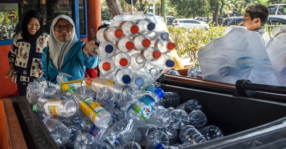 This picture taken on July 21, 2019 shows commuters exchanging plastic bottles for Suroboyo bus tickets at a terminal in the Indonesian city of Surabaya. (AFP Photo)