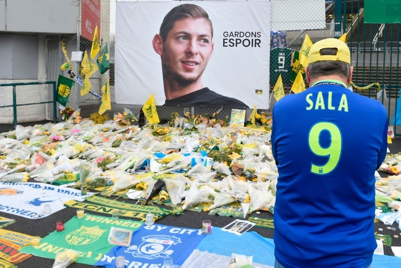 A supporter stands in front of flowers placed in front of a giant portrait of Argentinian former Nantes' forward Emilianio Sala outside La Beaujoire stadium (AFP Photo)
