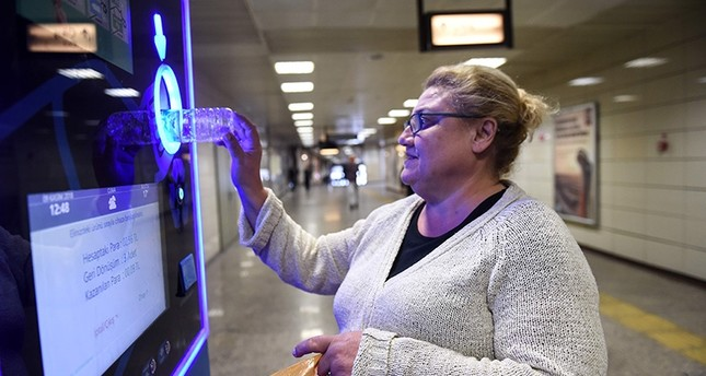 A woman puts a plastic bottle into a vending machine as she waits to take extra credit on her Istanbul card at Istanbul metro station on Nov. 9, 2018. (AFP Photo)