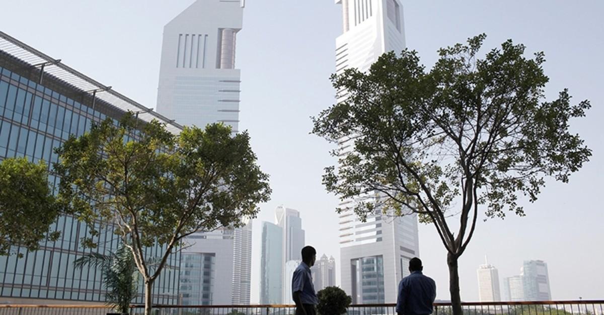 Men stand at the Dubai International Financial Center in Dubai May 5, 2013 (Reuters Photo)