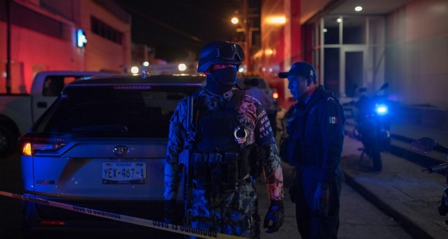 Federal forces keep watch at a crime scene following a deadly attack on a bar by unknown assailants in Coatzacoalcos, Mexico, Aug. 28, 2019. (AP Photo)