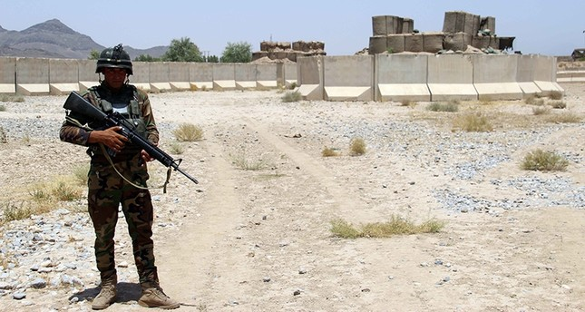 Afghan soldier secures a military base after overnight clashes with Taliban militants at a military base in Khakriz district, of Kandahar, Afghanistan, July 26,  2017. (EPA Photo)
