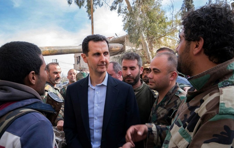 In this file photo released by the official Facebook page of the Syrian Presidency on March 18, 2018, shows Bashar al-Assad (c) talking with regime troops in eastern Ghouta. (AFP Photo)