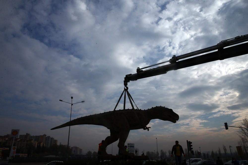 A crane hoists the dinosaur statue.
