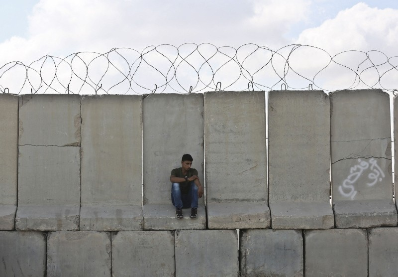 A Palestinian man sits on cement barricades as trucks carrying goods arrive at Kerem Shalom crossing in Rafah in the southern Gaza Strip on August 15, 2018.