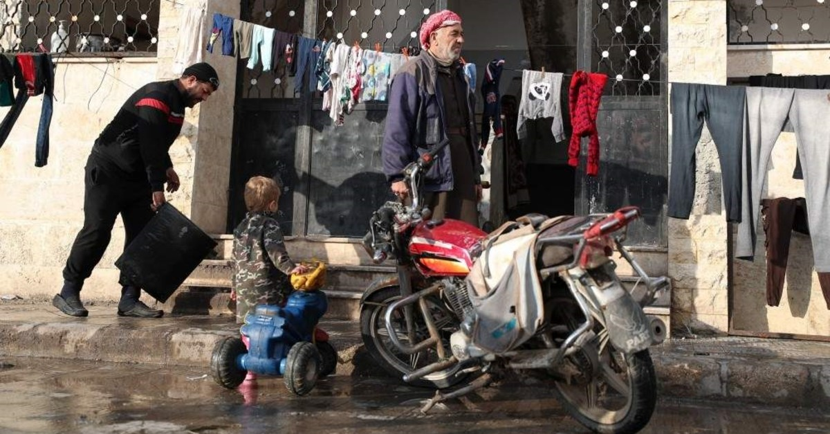 Abdul Razzak (R), a 65-year-old Syrian man displaced with his family from Maaret Al-Numa, looks on as his grandson plays at the entrance of a makeshift shelter in a former school building in Ariha town, in the south of Syria's northwestern province of Idlib, Dec. 31, 2019. (AFP PHOTO)