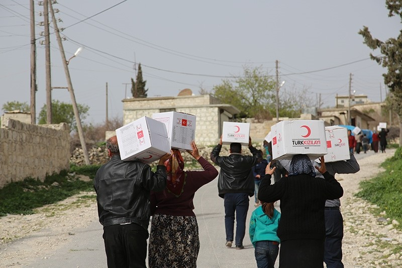 Afrin residents receive humanitarian aid packages distributed by the Turkish Red Crescent following the liberation of the Syrian city (AA Photo)