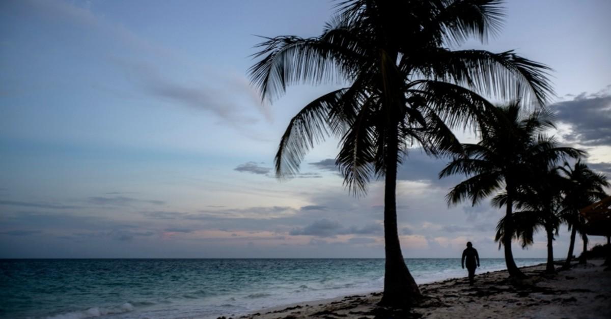 A woman walks along a beach before the arrival of Hurricane Dorian in Freeport, Grand Bahama, Bahamas, Saturday Aug. 31, 2019. (AP Photo)