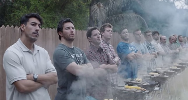 A screengrab from the new Gillette ad shows two kids wrestling while a long line of men stand in front.