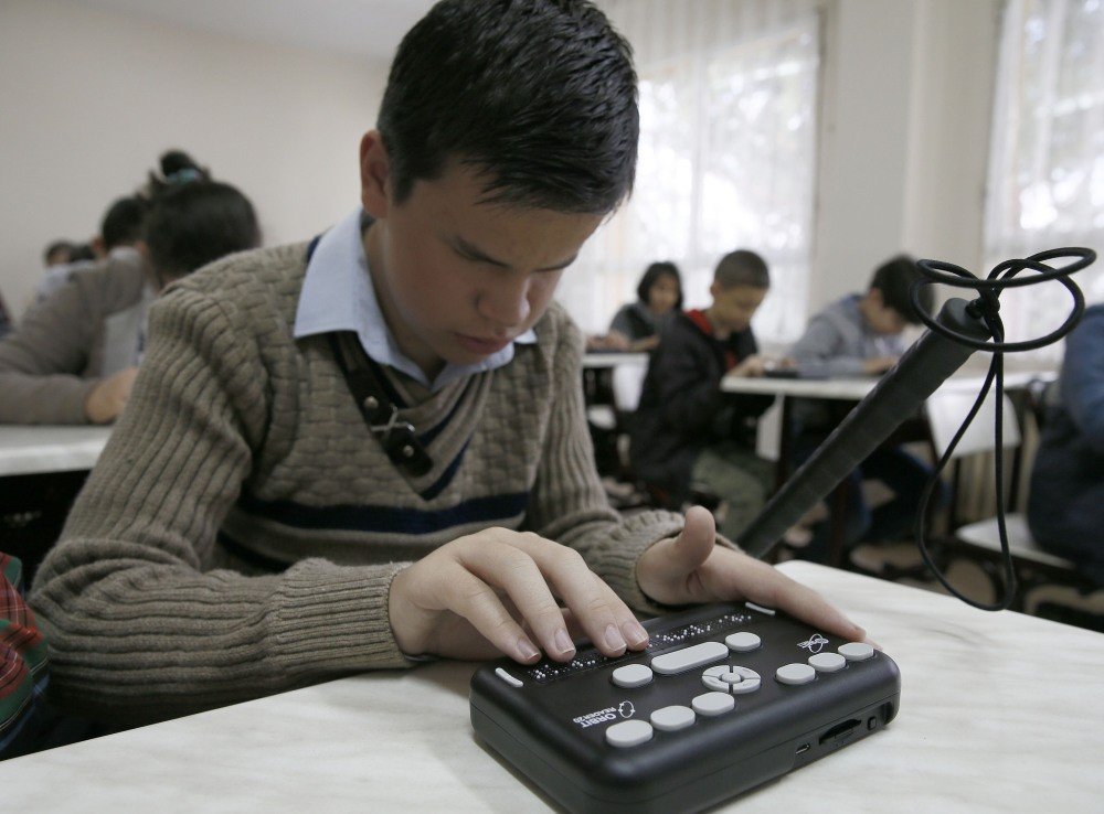 A student tries the device that will replace printed Braille books and allow them to translate anything.