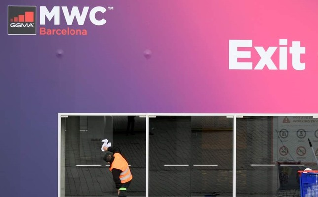 A worker cleans glass doors at the Mobile World Congress MWC venue on Feb. 12, 2020 at the Fira Barcelona Montjuic centre in Barcelona. AFP Photo