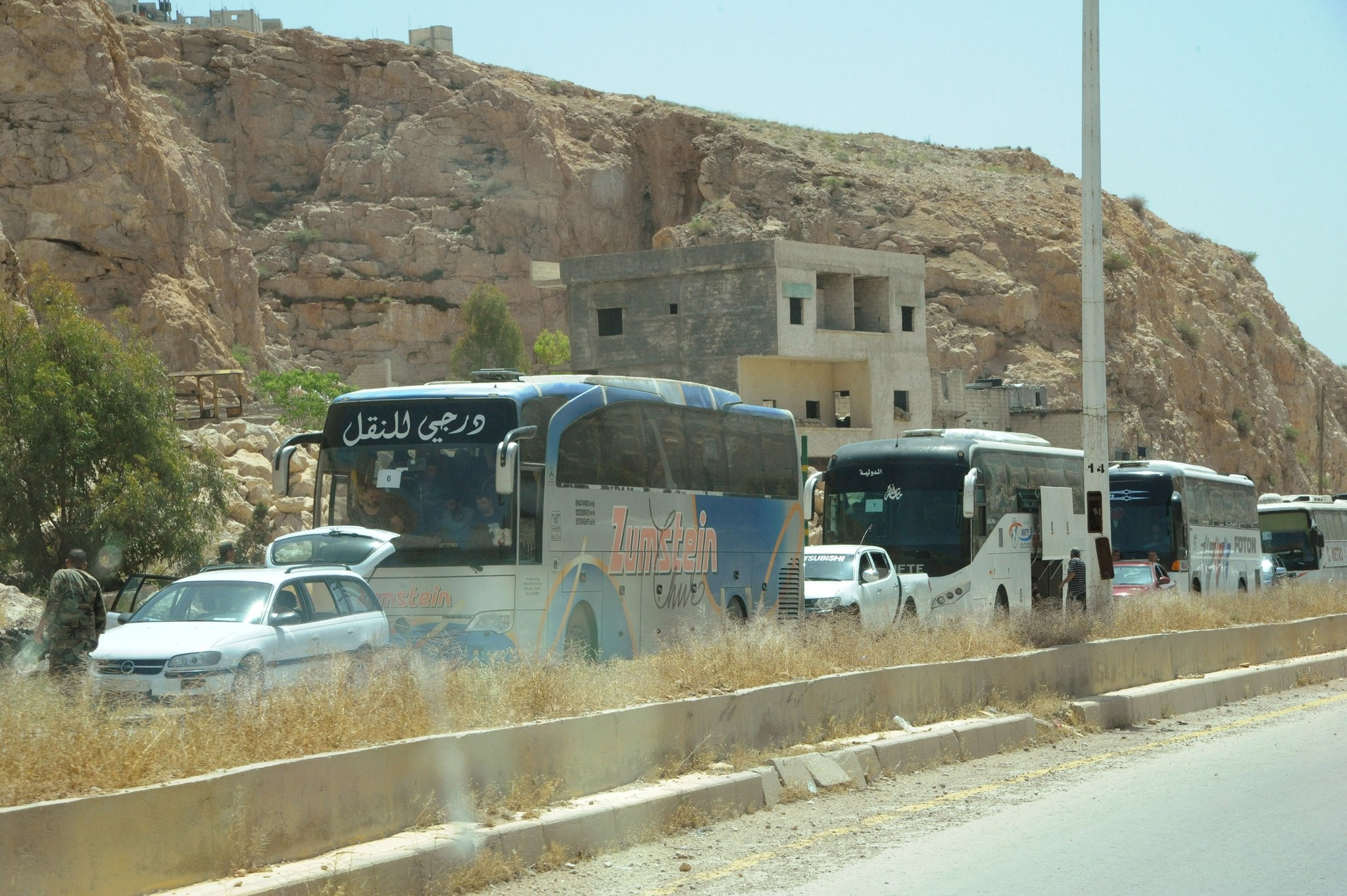 A convoy of buses carrying opposition fighters and their relatives from the besieged Damascus district of Barzeh. (SANA via Reuters)