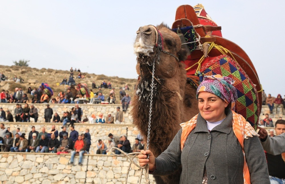 A camel breeder poses with her camel which will soon wrestle in the arena.