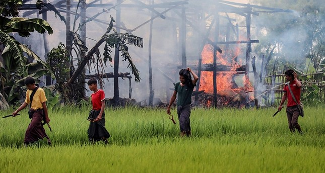 In this photograph taken on September 7, 2017, unidentified men carry knives and slingshots as they walk past a burning house in Gawdu Tharya village near Maungdaw in Rakhine state in Northern Myanmar (AFP Photo)