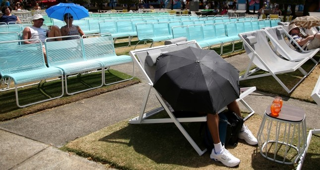 Spectators protect themselves from the heat with umbrellas as they watch tennis on a large video screen in Garden Square at the Australian Open tennis championships in Melbourne, Australia, Jan. 25, 2019. (AP Photo)