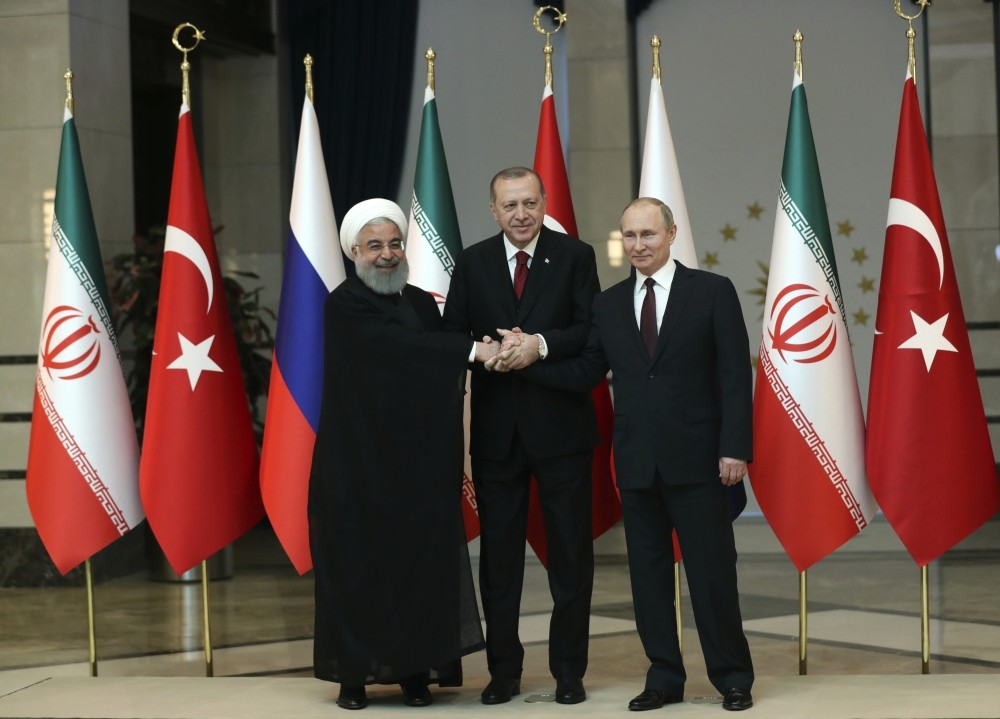 Iran's President Hassan Rouhani, (L), Russia's President Vladimir Putin, (R), and Turkey's President Recep Tayyip Erdou011fan shake hands during a group photo in Ankara, April 8.