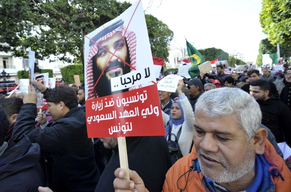 Tunisian protesters holding placards in Arabic that read ,Tunisians against the Saudi crown prince's visit,, shout slogans during a demonstration in Tunis, Nov. 27.