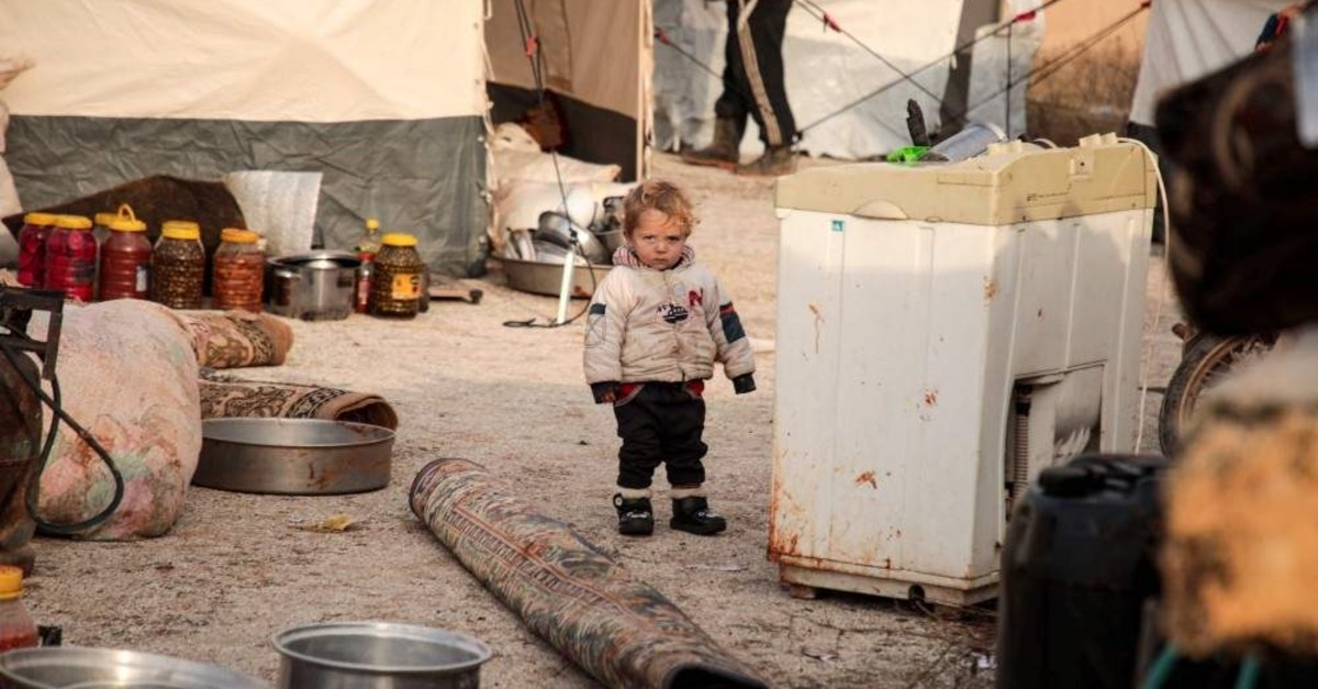 A Syrian child, one of those who fled from government forces' advance on Maaret al-Numan in the south of Idlib prvoince, walks by a rolled-up carpet and a washing machine in the open at a camp for the displaced near the town of Dana in the province's north near the border with Turkey, Dec. 27, 2019. (Photo by Aaref WATAD / AFP)