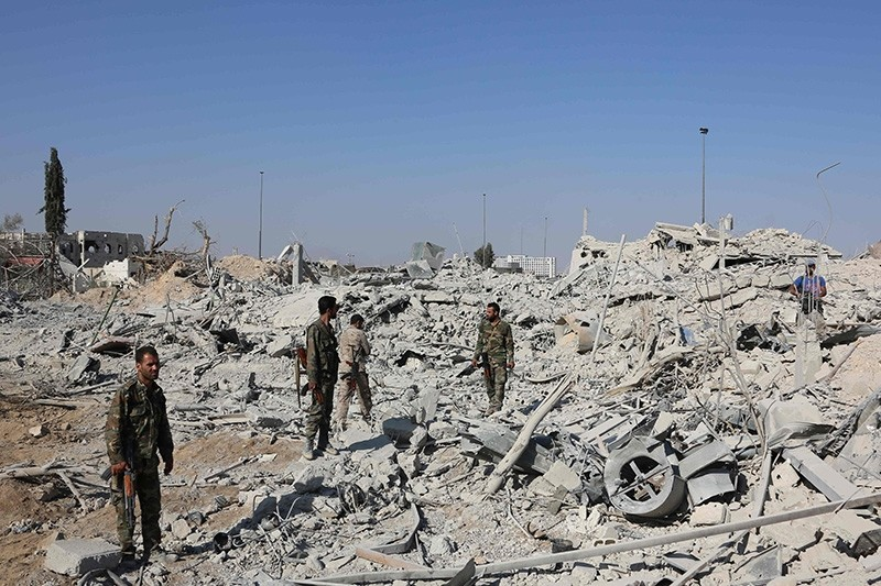 Assad regime forces stand on the rubble of destroyed buildings as they advance through Qabun district, on the outskirts of the capital Damascus, on May 13, 2017 (AFP Photo)