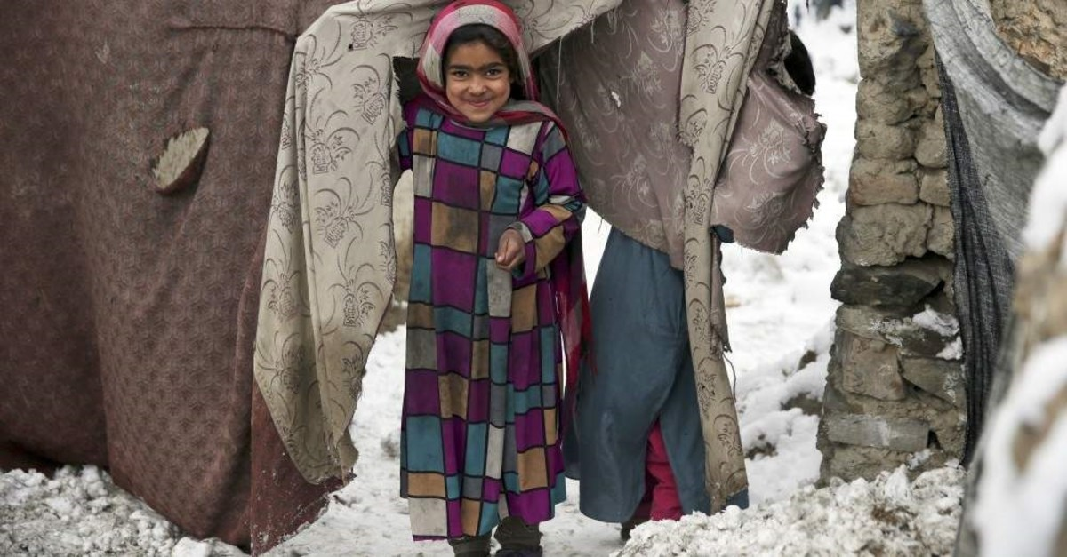 A young Afghan refugee peers from her temporary home after a snowstorm at a camp on the outskirts of Kabul, Jan. 12, 2020. (AP PHOTO)