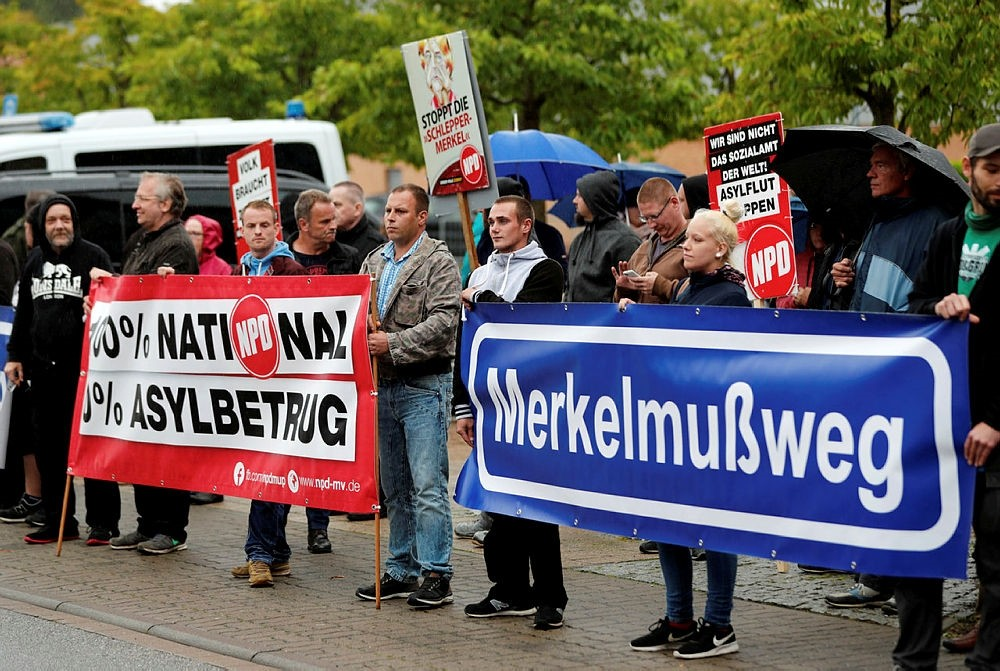 Protesters hold sign that reads ,Merkel must go, prior to the election campaign rally of German Chancellor Angela Merkel in Wolgast, Germany, September 8, 2017. (REUTERS Photo)