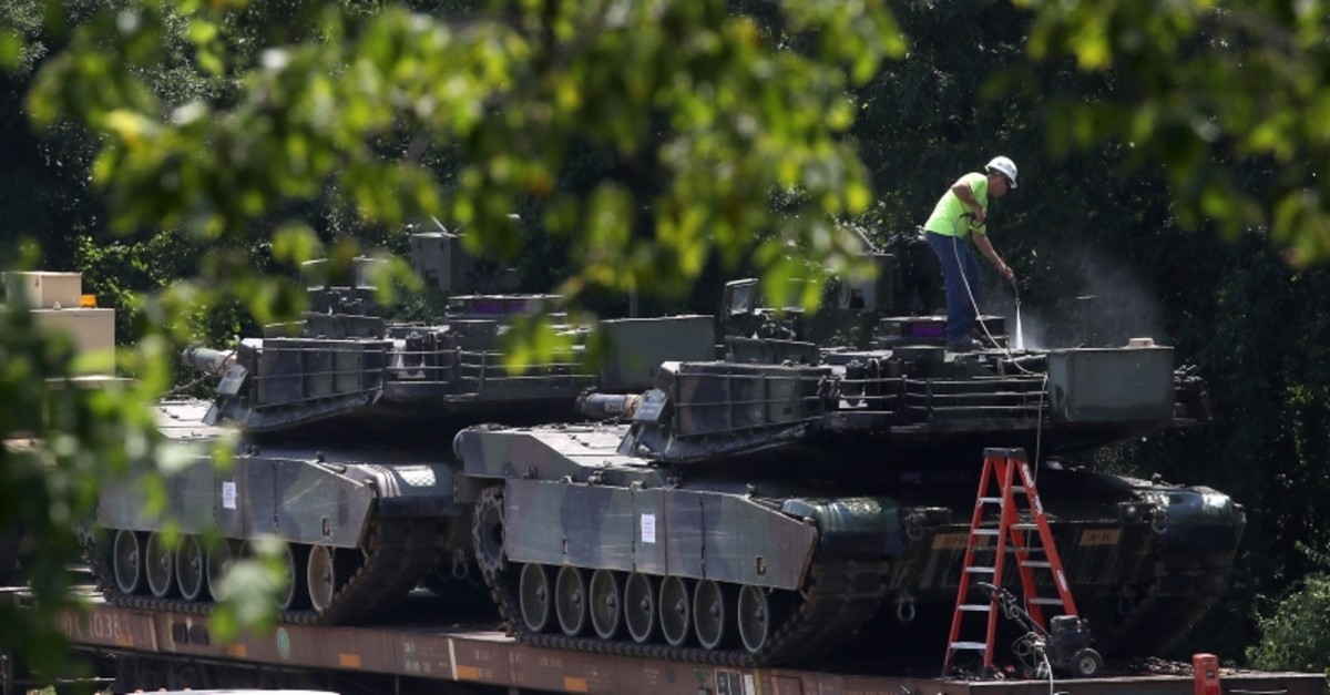 A worker washes one of two M1A1 Abrams tanks that are loaded on rail cars at a rail yard on July 2, 2019 in Washington, DC. (AFP Photo)