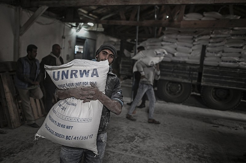 A Palestinian refugee carries a sack with flour at the United Nation food distribution center in al Shateaa refugee camp in the northern Gaza city, Jan. 15, 2018. (EPA Photo)