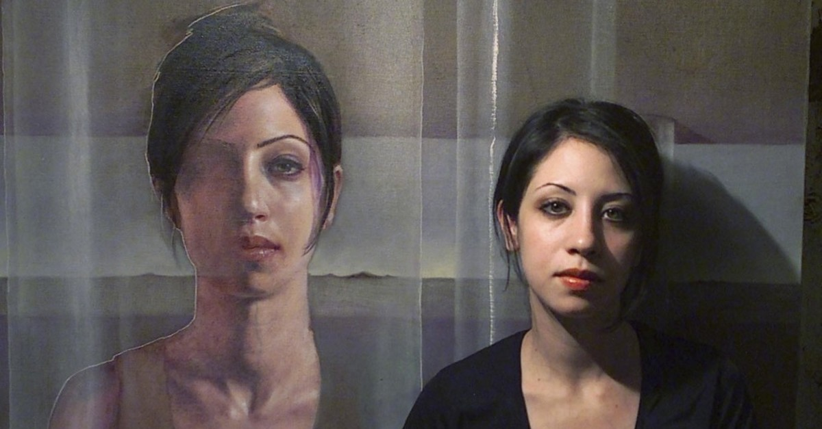 Sara Shamma stands beside a work of hers.
