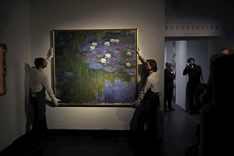 Christie's London auction house staff pose for photographs with Claude Monet's 'Nympheas en fleur' at their premises in London, Feb. 20, 2018. (AP Photo)