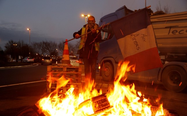 A protester wearing a yellow vest, the symbol of a French drivers' protest against higher diesel fuel prices, holds a flag with words To arms near burning debris at the approach to the A2 Paris-Brussels Motorway, December 4, 2018. (Reuters Photo)