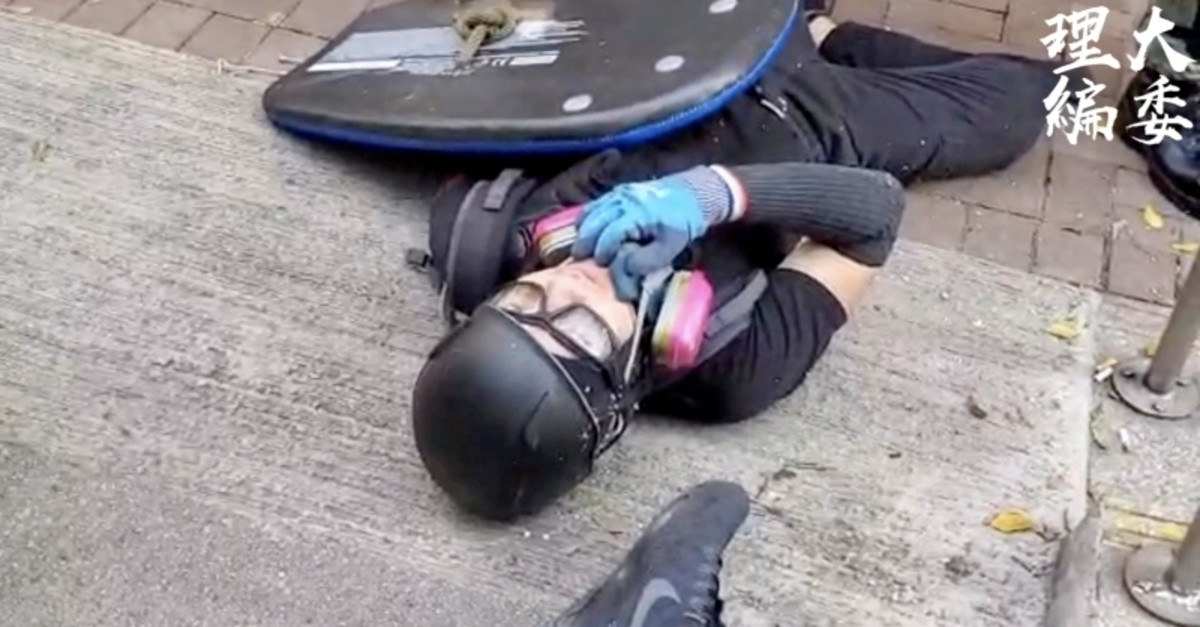 A protester lies with a gunshot wound outside Cheung Hing Kee Shanghai Pan-fried Buns in Hong Kong, China, Oct. 1, 2019 in this still image taken from a video. (HKPUSU Press Committee via Reuters)
