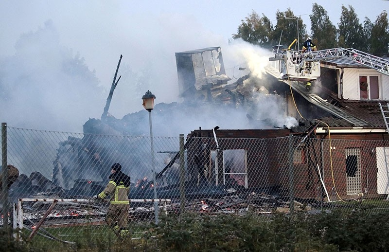 Firefighter stands in front of the smoldering ruins of a mosque building set on fire in the early hours of the morning on Sept. 26, 2017 in Orebro, Sweden. (EPA Photo)