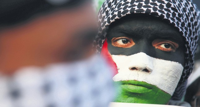 A protestor wears face print resembling the Palestinian flag during a rally against Trump's Jerusalem decision.