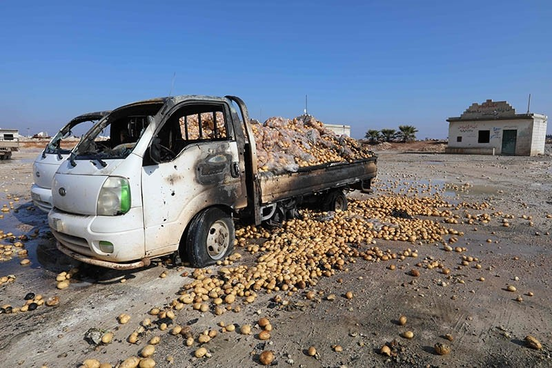 This picture taken Jan. 29, 2018 shows trucks loaded with potatoes standing abandoned after their windows were blasted from their frames following airstrikes by Assad regime forces which hit a vegetable market in Saraqeb, Idlib, Syria. (AFP Photo)