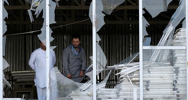 Afghan men look outside a broken window at the site of a suicide attack in Kabul, Afghanistan Sept. 9, 2018. (Reuters Photo)