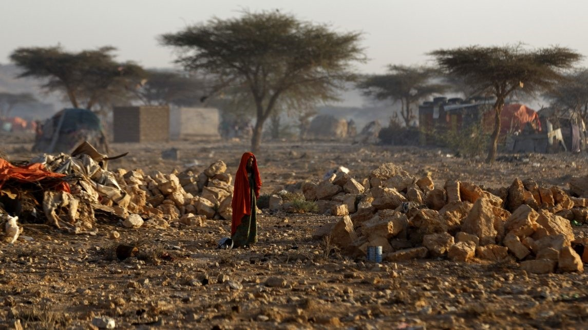 A Somali woman walks through a camp of people displaced from their homes elsewhere in the country by the drought, shortly after dawn in Qardho, Somalia on March 9.