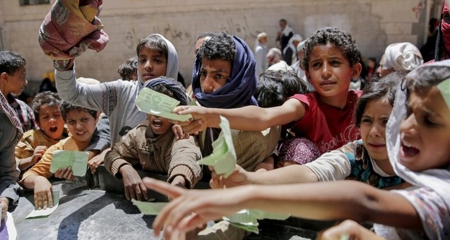 In this April 13, 2017, file photo, Yemenis present documents in order to receive food rations provided by a local charity, in Sanaa, Yemen. AP Photo