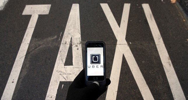 The logo of car-sharing service app Uber on a smartphone over a reserved lane for taxis in a street is seen in this photo illustration taken in Madrid on December 10, 2014 (Reuters Photo)