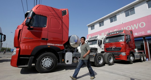 A man walks past liquefied natural gas (LNG) trucks for sale outside a heavy-duty truck shop in Yutian county, China's Hebei province.