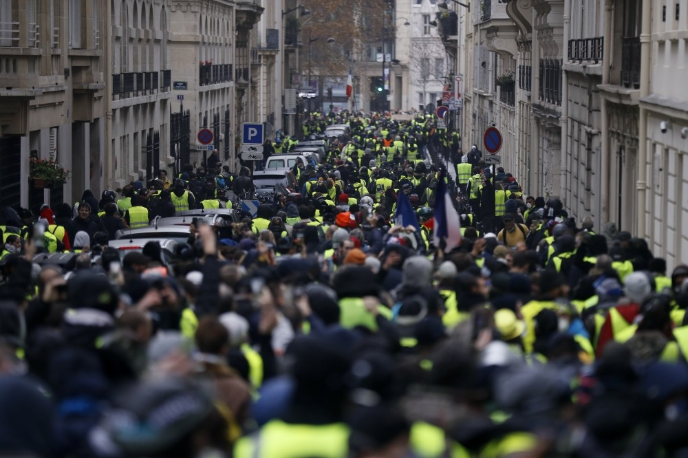 Protesters wearing iconic yellow vests during a rally near the Arc de Triomphe as riot police try to clear the area, as part of a demonstration over high fuel prices, the Champs Elysee, Paris, Dec.1.
