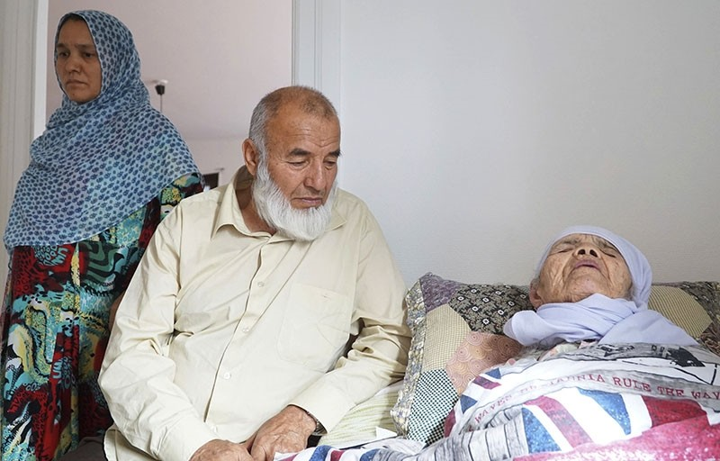 106-year-old Afghan refugee Bibihal Uzbeki rests in bed attended by her son Mohammadollah and daughter-in-law Ziba, in Hova, Sweden, Sunday, Sept. 3, 2017. (AP Photo)